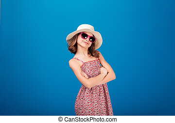 Lovely cheerful little girl in sunglasses standing with arms...