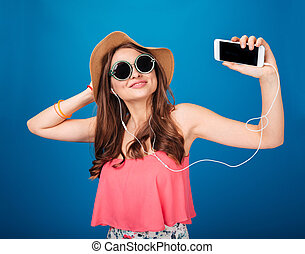 Smiling charming woman listening to music from blank screen smartphone