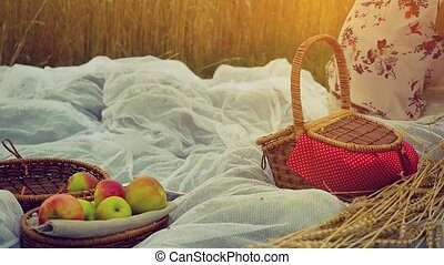 Young pretty woman on picnic listening to music in wheat...