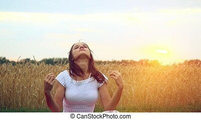 woman meditating on the field at sunset time in slowmotion...