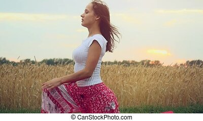 Beautiful young woman doing yoga exercise on wheat field in...