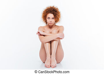 Woman with curly hair sitting on the floor