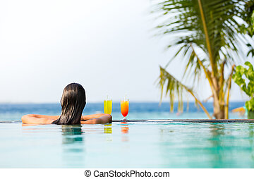 Brunette girl with cocktails in swimming pool - Brunette...
