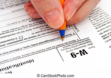 Person hand with pen filling in form W-9