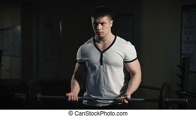 Closeup portrait of a muscular man workout with barbell at...