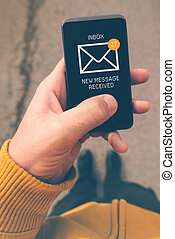 Using mobile smartphone to access e-mail inbox, man viewing...