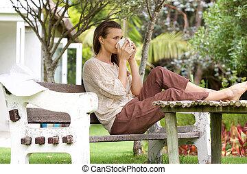 Woman drinking tea outside in backyard