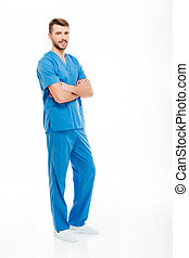 Happy male doctor standing with arms folded - Full length...