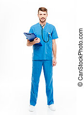 Happy male doctor standing with clipboard - Full length...