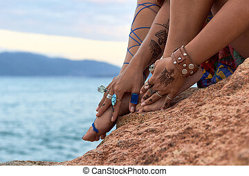 girls hands with feet, mehendi,accessories, on mountain sea...