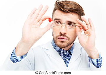 Male doctor in glasses looking on pill - Young male doctor...