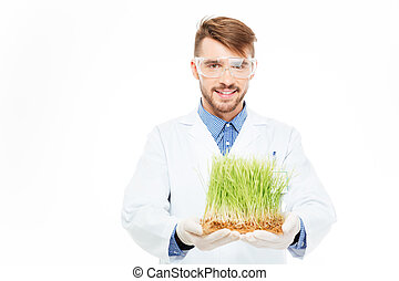 Happy male engineer showing a modified plants isolated on a...