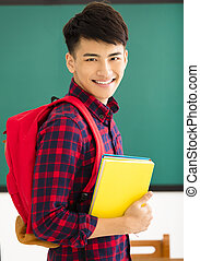Smiling male student standing in  classroom