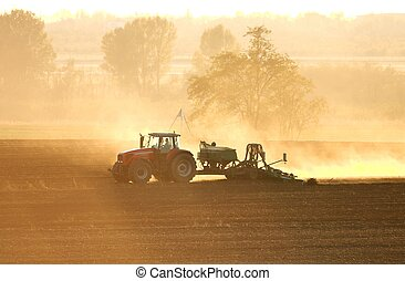 Tractor in sunrise plowing the field