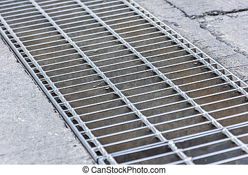 Black and white close up of a sidewalk subway grate with...