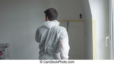 man at work in new home - young man painting his new home,...