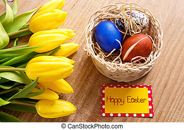 Happy Easter card and yellow tulips. - Basket of colorful...