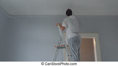 woman on ladder at work - attractive woman decorating her...