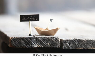 Start today concept - Start today text and a paper boat on a...