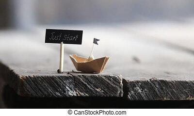 Just Start concept - Just Start text and a paper boat on a...