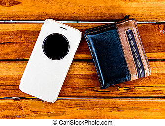 Mobile and wallet are on the wood,Focus on moble and wallet...