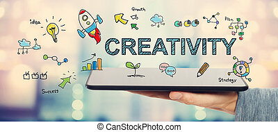 Creativity concept with man holding a tablet
