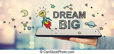 Dream Big concept with man holding a tablet