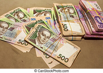 Many Ukrainian money hryvnia. Handcuffs on the money. Corruption in Ukraine. The fight against corruption. Physical evidence of corruption in government and business in the country
