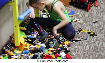 Child Boy Playing with Toys - Child boy sitting on the floor...
