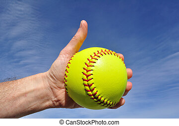 Softball Player Giving Thumbs Up Sign Against a Blue Sky