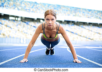 Young sportswoman is at large modern stadium - Young...
