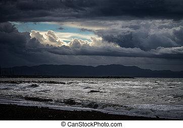 Sunny window between stormy clouds over mediterranean sea