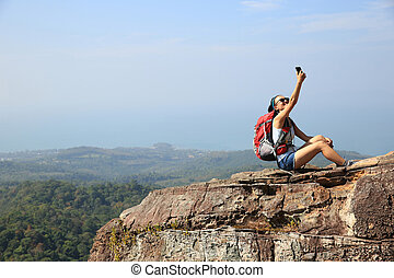 young woman backpacker taking photo with cellphone on...