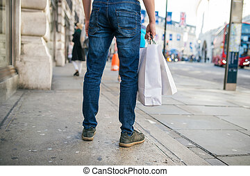 Unrecognizable man with shopping bags in the street, back...