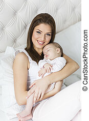 Happy mother with baby on bed