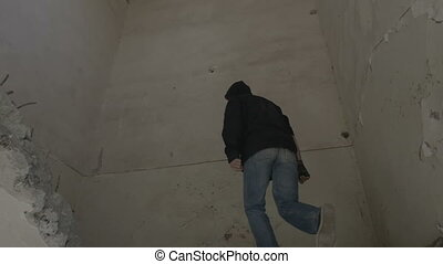 Hooded young man climbing the stairs of an abandoned...
