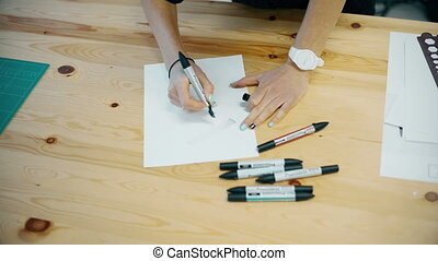 woman draws felt-tip pens on paper - Young Woman Hand with...