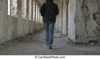 Hooded frightened young man running in an abandoned military...