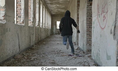 Hooded desperate young man running in an abandoned building