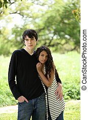Young teen couple holding each other outdoors portrait