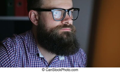 Man working at the computer - Tired young bearded man...