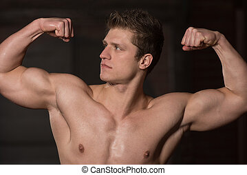Healthy Young Man Showing His Well Trained Biceps - Portrait...