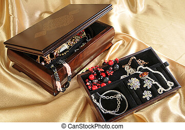 Wooden box with jewelry on golden background