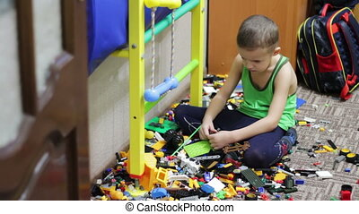 Upset Child Boy Playing with Toys.