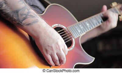 Man with Tatoo playing acoustic guitar - Guitarist with...