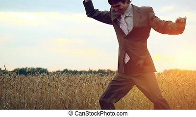 Happy businessman dancing in a field during sunset in...