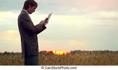 Businessman standing on a wheat field using a tablet....