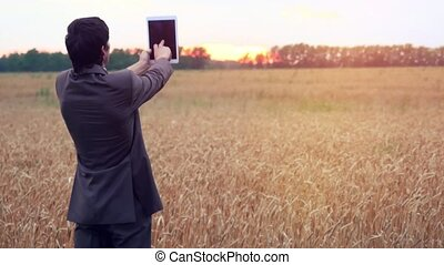 Businessman standing on a wheat field using a tablet...