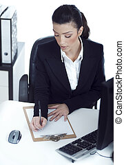 Busy business lady making her notes on the clipboard