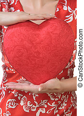 Woman holds a red heart opposite the bust